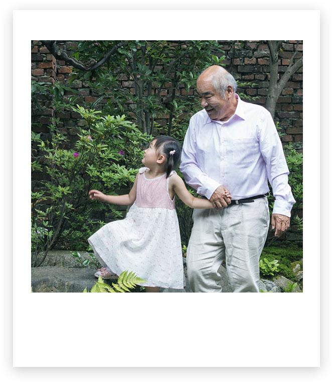 Imagen de un abuelo con su nieta que se cogen de la mano al aire libre.