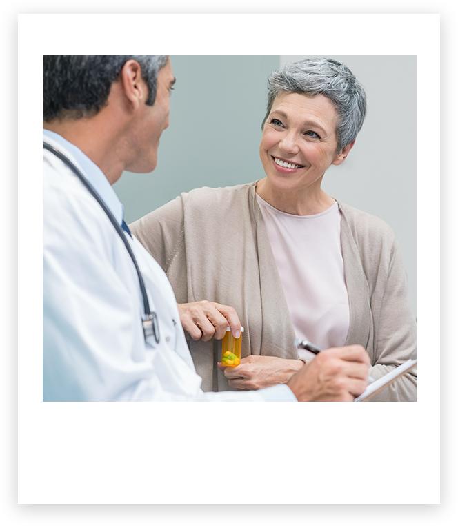 Imagen de un médico hablando con una paciente que sonríe.
