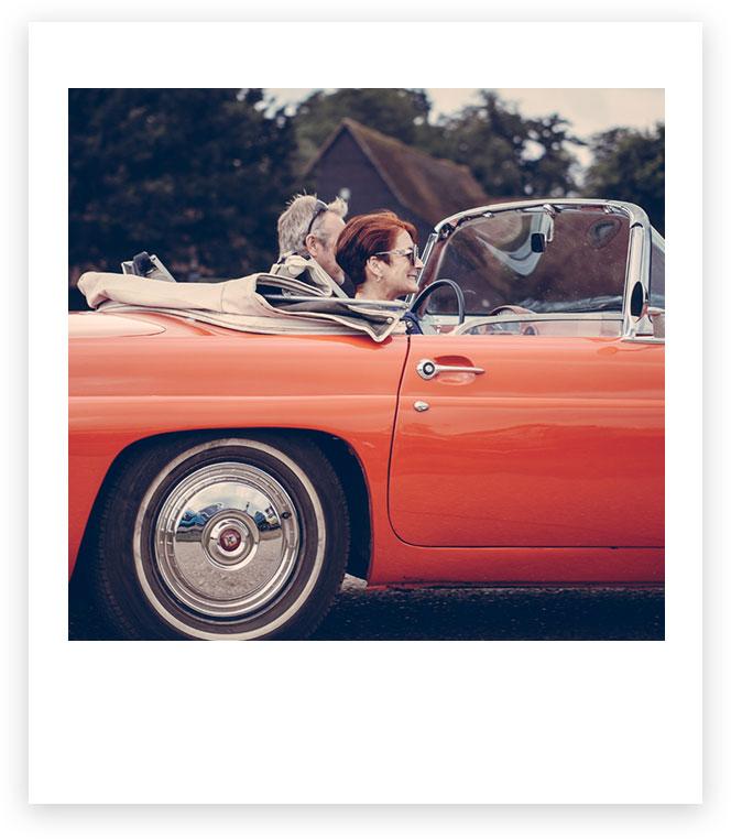 Imagen de una pareja en un descapotable rojo.