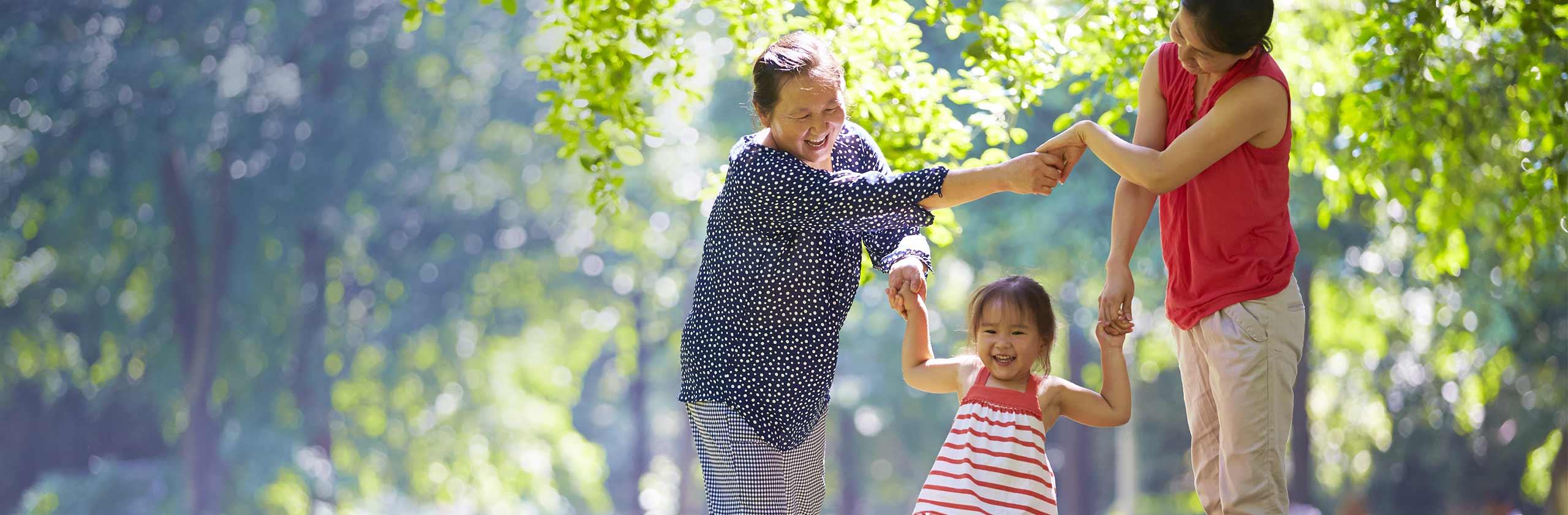 Imagen de una familia feliz cogida de las manos mientras da un paseo al aire libre.