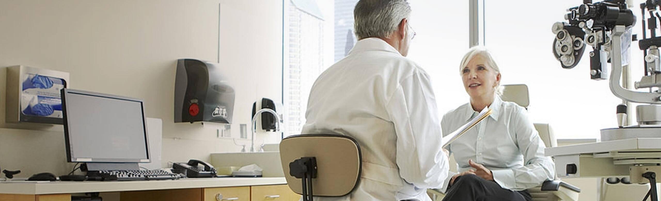 Imagen de oftalmólogo y paciente hablando en la sala de exploración.