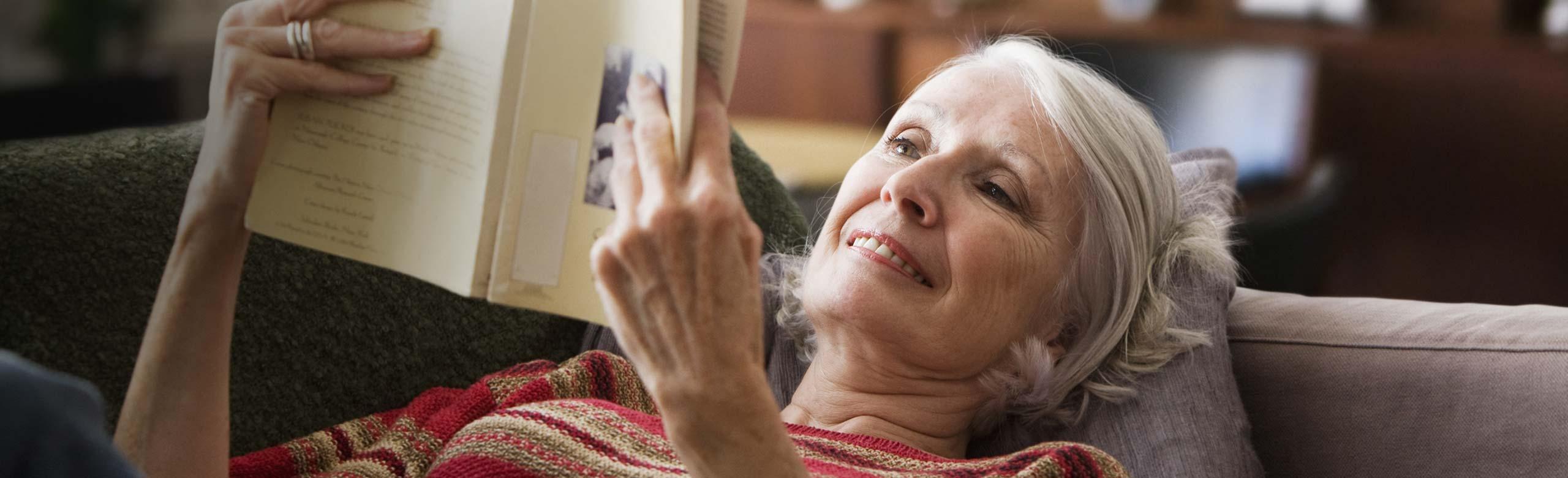 Imagen de una mujer tumbada en el sofá leyendo un libro.