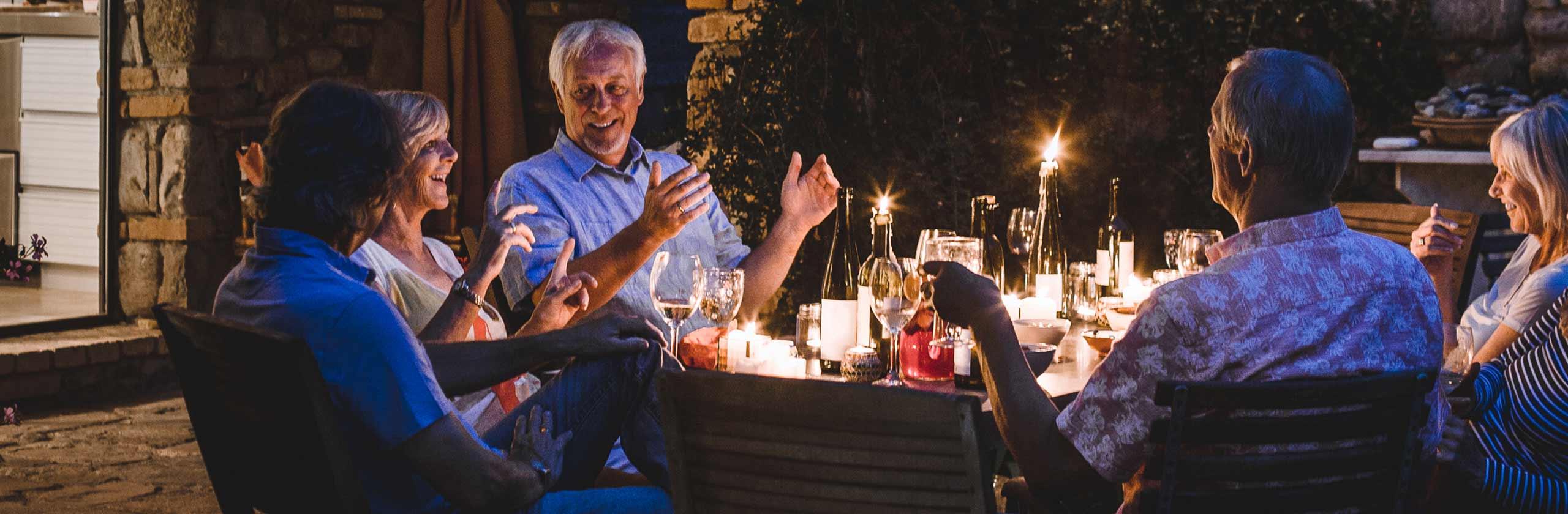 Imagen de personas reunidas en una mesa al aire libre