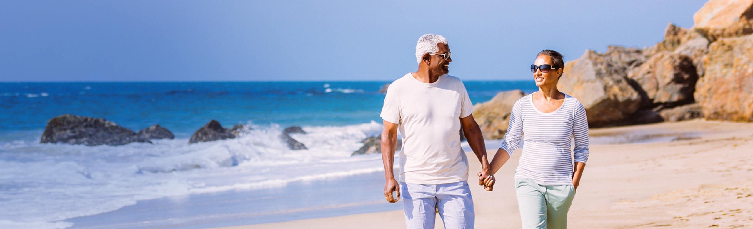 Imagen de una pareja que se coge de la mano en la playa.