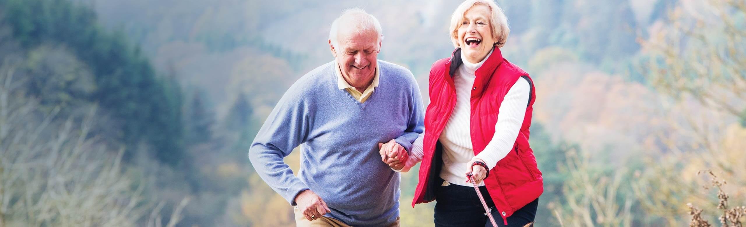 Imagen de un hombre y una mujer que pasean al aire libre mientras se cogen de la mano y ríen.