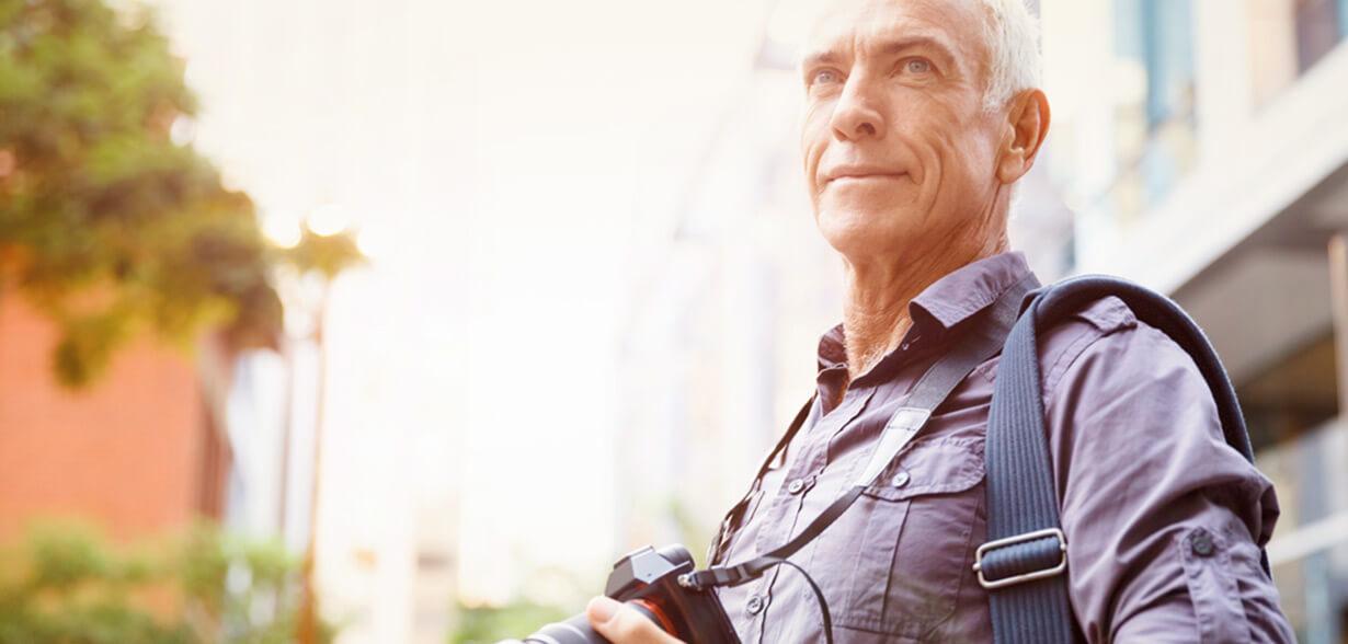 Imagen de un hombre con una cámara colgada al cuello.