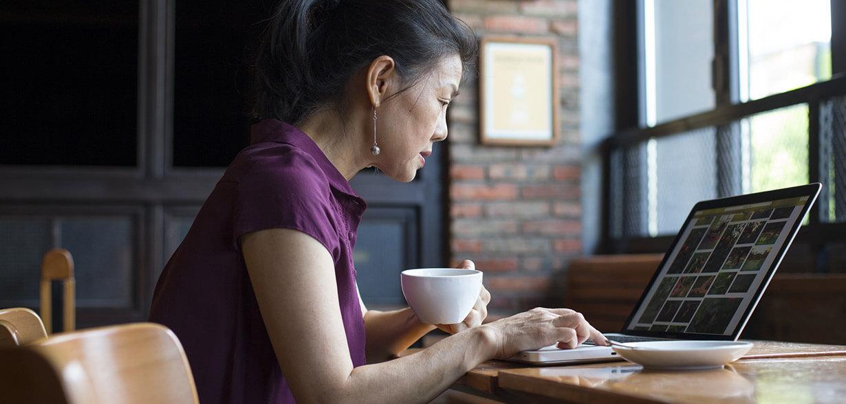Imagen de una mujer tomando un café mientras trabaja con un portátil.