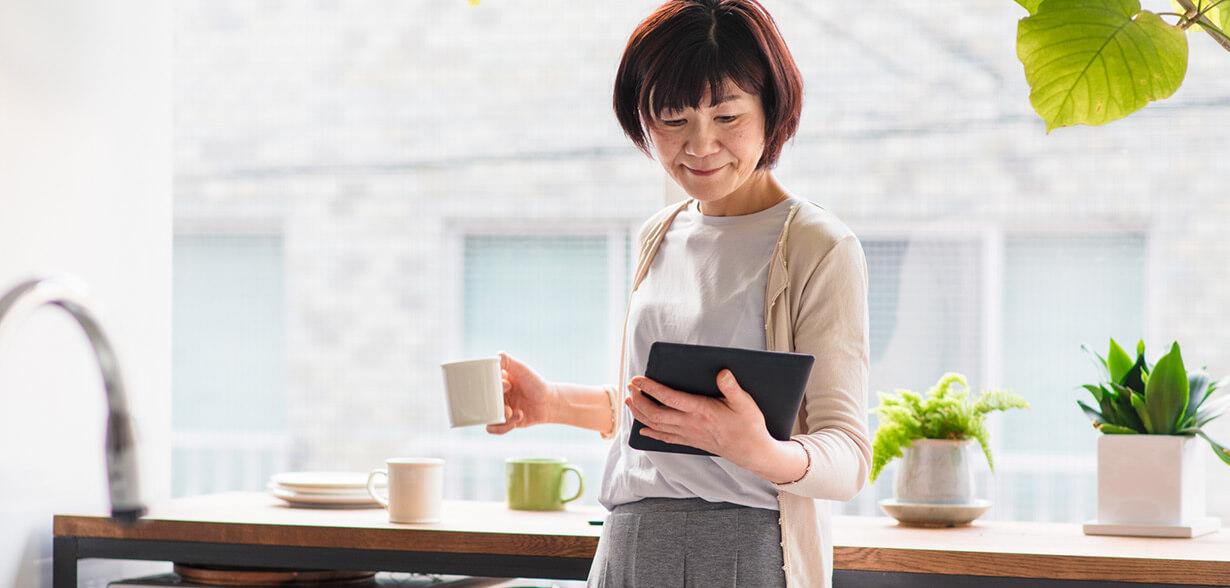 Imagen de una mujer con una taza de café y usando la tableta.