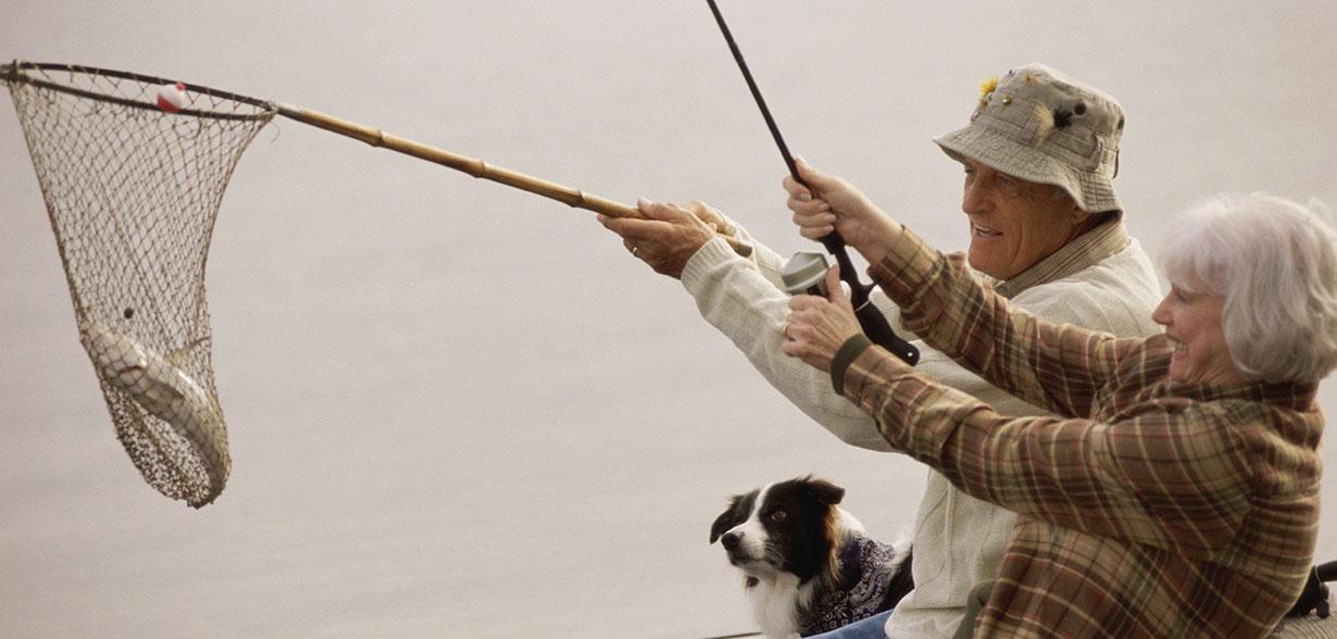 Imagen de una pareja de ancianos que está pescando con una red y una caña de pescar.